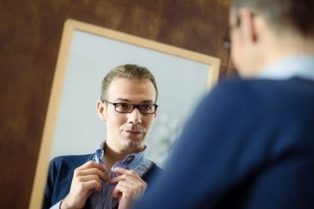 Guy fixing tie in mirror for first date