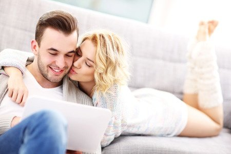 a picture of a romantic couple with laptop in living room