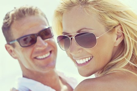photograph of happy and attractive man and woman couple wearing sunglasses and smiling in sunshine at the beach