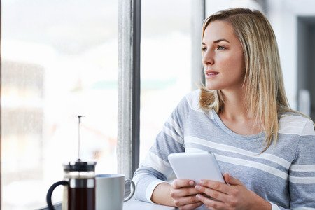 young businesswoman working on tablet computer while drinking coffee in the office